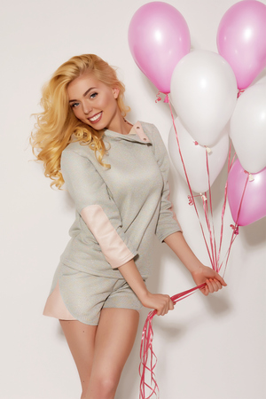 sport clothes: Beautiful smiling blond girl in casual sport clothes  with curly hair holding white and pink helium balloons on a white background at the studio