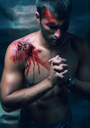 hemorragias: Retrato de guapo masculino sangrado hombre con sangre en la cara y el hombro labios usando jeans y ver que rezar y verse como católica