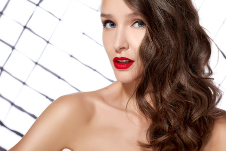 Sexy young beautiful girl with dark curly hair with red lips and blue eyes bright makeup bare shoulder playfully looks at the camera on a white background with a bright light photo