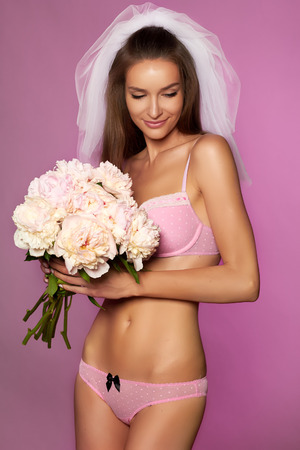white lingerie: Pretty young sexy fiancee in white veil and pale pink lace lingerie with bouquet of peonies in hand Stock Photo