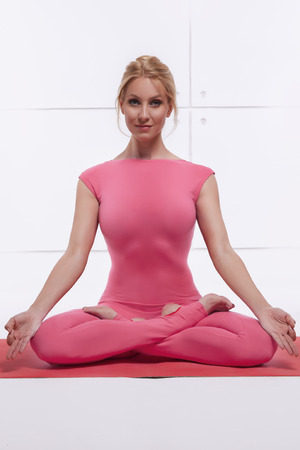 Beautiful attractive sexy blond woman doing yoga sitting in the lotus position relaxes and opens the chakras dressed in comfortable fitting suit pink photo
