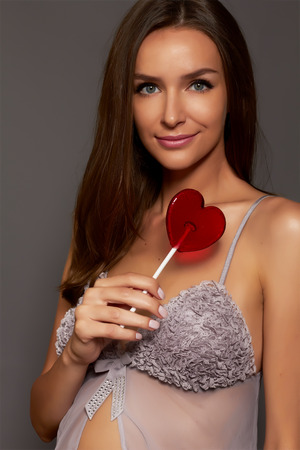 Beautiful pregnant girl with a gray silk lace nightgown with a cut and bow in front of the anticipation of a toddler holding a lollipop in the shape of a red heart photo