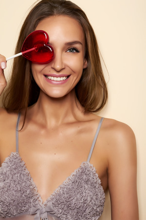 Beautiful young sexy girl with natural brown hair with a gentle makeup bare tanned shoulder straps and a thin gray looking away and covers one eye candy in the form of red heart