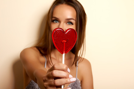 Beautiful young girl with dark hair in a gray dressing gown stretches forward shaped lollipop red heart candy on a stick in focus, girl is blurred on the background