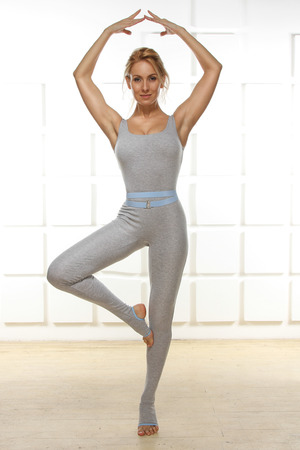 Beautiful sexy blonde with perfect athletic slim figure engaged in yoga, exercise or fitness, lead a healthy lifestyle, and eats right, dressed in comfortable casual clothes ballerina standing in a pose of hands up photo