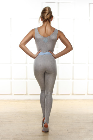 Beautiful sexy blonde with perfect athletic slim figure engaged in yoga, exercise or fitness, lead a healthy lifestyle, and eats right, dressed in comfortable casual clothes standing with his back photo