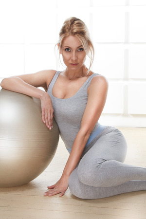 Beautiful sexy blonde with perfect athletic slim figure engaged in yoga, exercise or fitness, lead a healthy lifestyle, and eats right, dressed in comfortable casual clothes sitting next to ball sports photo