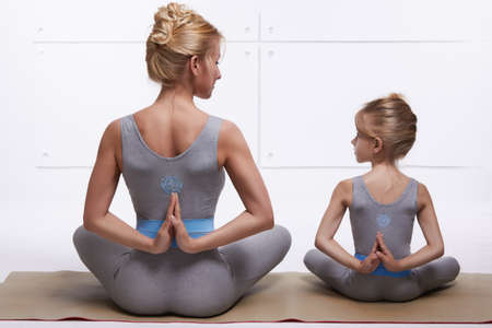 synchronously: Mother and daughter doing yoga exercise, fitness, gym wearing the same comfortable tracksuits, family sports, sports paired