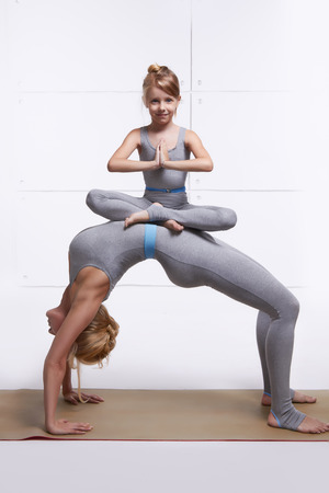 tumbling: Mother and daughter doing yoga exercise, fitness, gym wearing the same comfortable tracksuits, family sports, sports paired