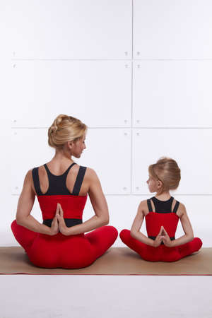 footwork: Mother and daughter doing yoga exercise, fitness, gym wearing the same comfortable tracksuits, family sports, sports paired