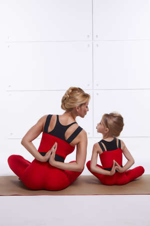 Mother and daughter doing yoga exercise, fitness, gym wearing the same comfortable tracksuits, family sports, sports paired photo