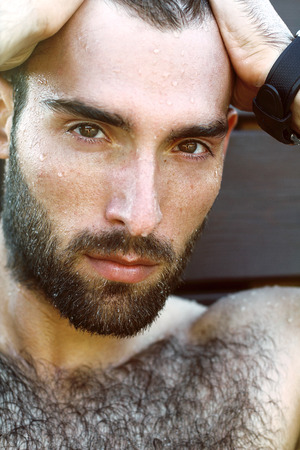 hairy chest: Fashion Portrait of handsome masculine guy with drop of water on а face with Brown dark eyes Beard and mustache