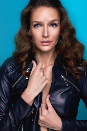 Fashion portrait of the frighting beautiful girl with shining tanned skin and Big Blue Bright eyes and curly hair on a blue background and holding leather jacket with a silver zippers photo