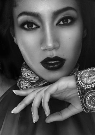 Black and white fashion portrait of the beautiful mulatto whith dark skin, hair and red lips in traditional ethnic accessories, and bracelet on her hand