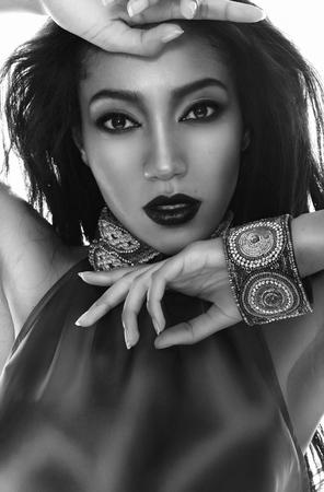 dark skin: In bianco e nero Ritratto di moda della bella whith mulatto pelle scura, i capelli e le labbra rosse in accessori etnici tradizionali, e bracciale sulla sua mano Archivio Fotografico