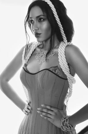 dark skin: In bianco e nero Ritratto di moda della bella whith profilo mulatto pelle scura e labbra rosse in corde corsetto lingerie e blu corral sul suo collo e la mano su uno sfondo bianco