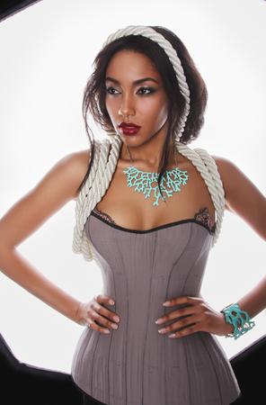 modelo sexy: Retrato de moda de la hermosa mulata poco con la piel oscura y los labios rojos en las cuerdas del cors� de la ropa interior y azul corral en el cuello y la mano sobre un fondo blanco