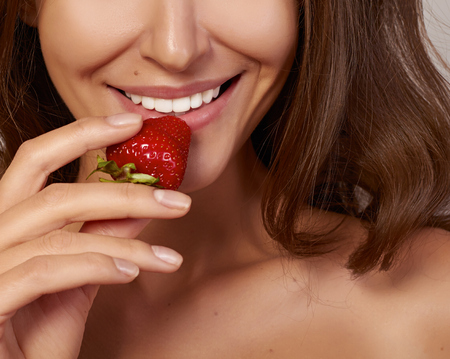nouse: Beatiful girl with Perfect smile eat red strawberry  white teeth and healthy food