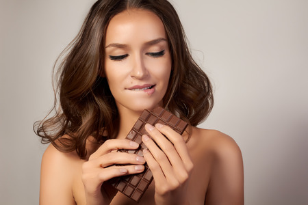 aliment: Portrait of a young beautiful girl with dark curly hair, bare shoulders and neck, holding a chocolate bar to enjoy the taste and are dieting, healthy eating and organic foods, feeling temptation