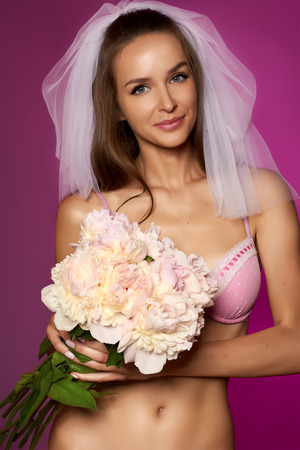 undies: Beautiful young sexy bride with nice shape in white veil and pale pink lace lingerie with bouquet of peonies in hand