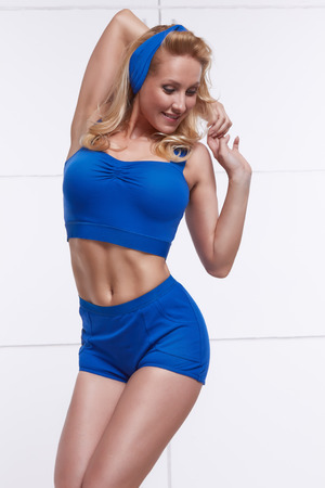 Young blonde dressed in style PinUp tanned body fitness sport photo