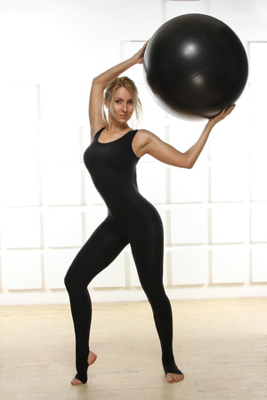 Beautiful young attractive beautiful woman with blond hair standing holding up ball photo