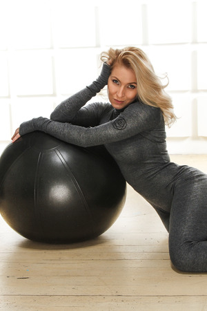 Beautiful young attractive beautiful woman with blond hair standing holding up ball for fitness  photo