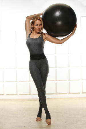 exercitation: Beautiful young attractive beautiful woman with blond hair standing holding up ball for fitness