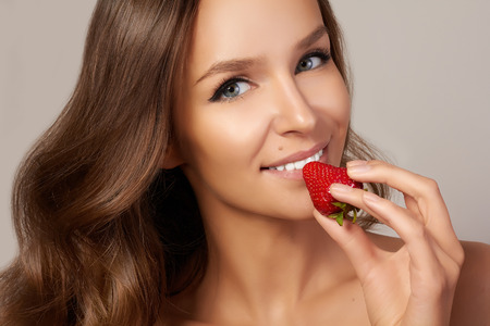 nouse: Beatiful girl with perfect smile eat healthy food red strawberry