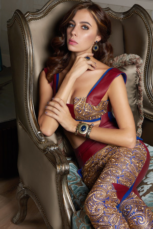 Beautiful sexy brunette woman with wavy hair in a bright multi-colored suit on the wide shoulder straps with rings bracelets accessories