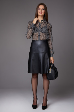 leather skirt: Beautiful sexy young business woman with evening make-up wearing a skirt to the knee and a silk blouse with lace long sleeves and high-heeled shoes and a small black handbag, business clothes for meetings and walks