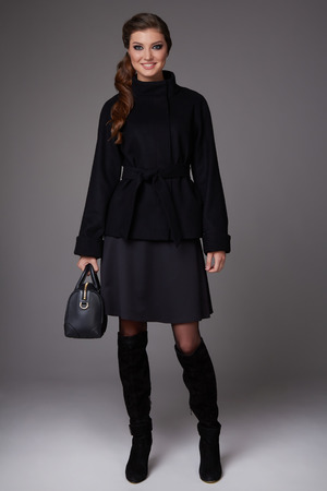 Beautiful sexy young business woman with evening make-up wearing a skirt to the knee wool coat jacket high svpogi high heels and a small black handbag, business clothes for meetings and walks autumn collection photo