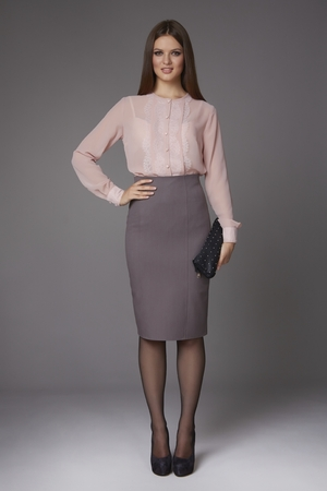 Beautiful sexy young business woman with evening make-up wearing a skirt to the knee and a silk blouse with lace long sleeves and high-heeled shoes and a small black handbag, business clothes for meetings and walks