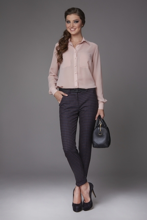 Beautiful sexy young business woman with evening make-up dressed in tight pants and silk blouse with lace long sleeves and high-heeled shoes and a small black handbag, business clothes for meetings and walks Imagens