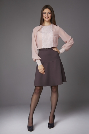 Beautiful sexy young business woman with evening make-up wearing a skirt to the knee and a silk blouse with lace long sleeves and high-heeled shoes and a small black handbag, business clothes for meetings and walks photo