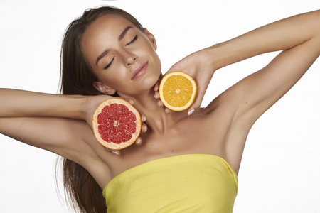 bare shoulders: Beautiful sexy young woman wit perfect healthy skin and long brown hair day makeup bare shoulders holding orange lemon grapefruit healthy eating organic food diet weight loss