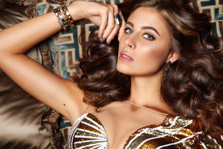 novae: Beautiful sexy brunette woman with wavy hair in a bright multi-colored suit on the wide shoulder straps with rings bracelets accessories, or evening hairstyle and makeup sitting in chair with cushions
