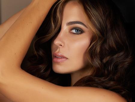 body paint: Joven y bella mujer de noche sexy maquillaje ojo pesta�as oscuras te�ido olas morena apilados pelo ogoleno-hombro Golden Tan mira en la c�mara de la parte posterior
