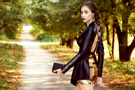 novae: Woman walking in park dressed in lather jacket and gold short