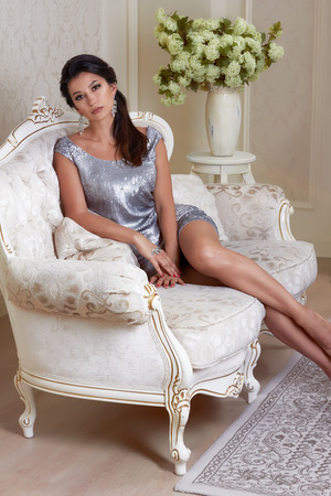 chic woman: Sexy beautiful young brunette woman with evening make-up chic groomed wearing a short evening dress embroidered with silver sequins and earrings sitting on the couch in background with flower Stock Photo
