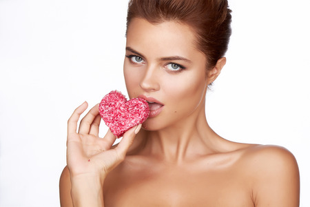 sexy food: Beautiful sexy brunette woman eating cake shape of heart on a white background, healthy food, tasty, organic, romantic valentine day