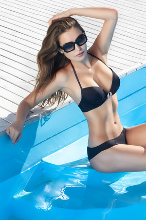 Beautiful sexy young girl with perfect slim figure with long wet hair and bathing suit in fashionable stylish sun glasses sitting on the steps of swimming pool swim, sunbathe, have fun at beach party Stock Photo