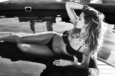 Black and white photo of beautiful sexy blonde woman laying near the swimming pool in black suite and bracelet and colorful beads photo