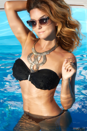 Beautiful blonde or red girl with perfect tan skin with golden big necklace on the neck staying in wet black swimming suite and brown sunglasses inside of water in swimming pool with light blue water photo
