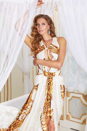 dimond: Beautiful sexy young blonde woman with long curly hair and make-up wearing a long evening dress white with gold embroidery and jewelery and accessories worth of white curtains in the bedroom is going to a party or a red carpet