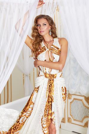 cortinas blancas: Hermosa joven rubia sexy con el pelo largo y rizado y maquillaje que llevaba un vestido de noche largo blanco con bordados de oro y joyas y accesorios por valor de cortinas blancas en el dormitorio va a una fiesta o una alfombra roja Foto de archivo