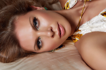 Beautiful young blonde woman in green earrings red nails silver ring and blue big stone with and perfect silk skin and natural make-up laying on the bed in evening white dress with wild leopard print
