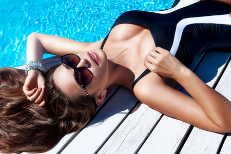 sunglasses beach: Beautiful sexy young woman with perfect slim figure with long dark hair and wet bathing suit fashion in stylish glasses from the sun is sunning by swimming pool swim, sunbathe have fun at beach party Stock Photo