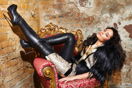 Beautiful sexy woman long brunette hair in black fur Treads on high heel gold pans sitting on the chair red brick wall background makeup fashion style Stockfoto
