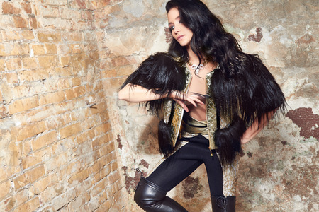 Beautiful sexy woman long brunette hair in black fur and Leather trousers near yellow and red brick wall on background in rock style